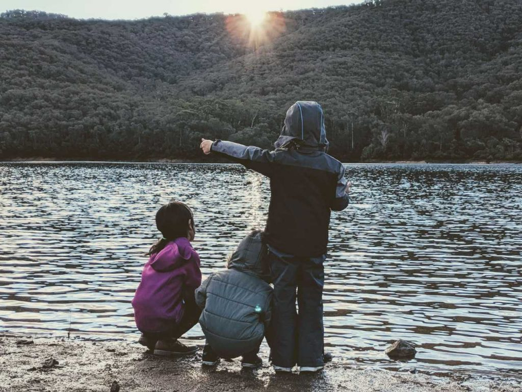 Kids standing in front of lake and mountains