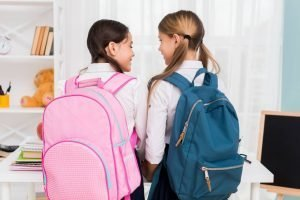 School girls with backpacks looking at each other
